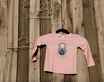 size 2 pink long sleeved top featuring a hand embroidered applique of a babushka doll