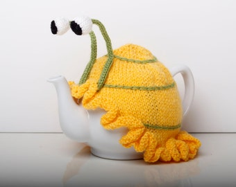 Knitted yellow snail tea cosy with frilly bottom. Washable fits 1 litre teapot.