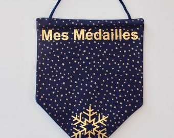 flag hangs medals of skiing in the fabric. Navy Blue and gold. Snowflake.