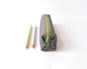 Small pencil case/zipper pouch in dark green with small white dots, with a forest green zip, and a blue, yellow and green striped lining