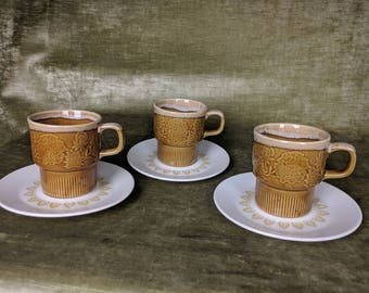 Set of three unique stacking mugs with saucers