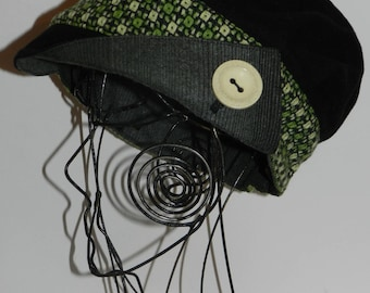 """Black and green cap newsboy style with asymmetrical visor """"buttoning""""."""