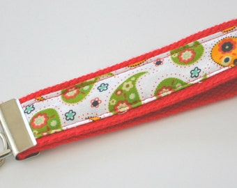 Olive, Rust, Yellow Orange Paisley Fabric Wristlet Keychain on a Red Heavy Duty Cotton Webbing