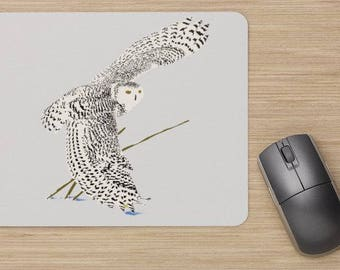 Mouse pad, the snowy owl in flight with his wing touching the snow.