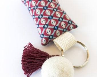 Key ring in fabric decorated with hand-stitching and pendants