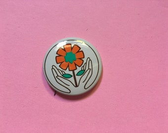 hands holding flower environmentalist pinback button