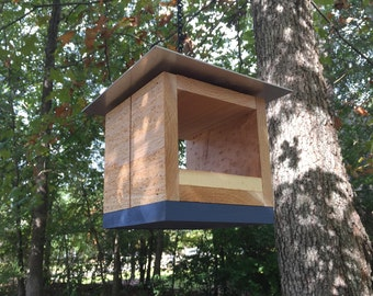 Cube-shaped bird feeder in natural cedar with aluminum roof and dusty-blue accent. Backyard, patio, or deck bird feeder for small birds.