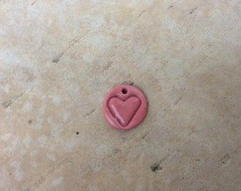 Small pink porcelain enamel medal.