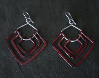 geometric copper and silver earrings with red patina