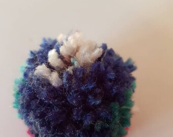 A handmade multi-coloured Pom Pom brooch with a safety brooch pin