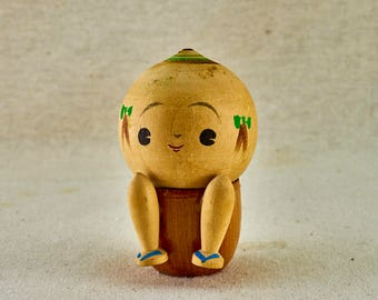 Kokeshi wooden doll. A child wearing a geta sandals sits on a potty. Vintage Japanese Kokeshi doll.
