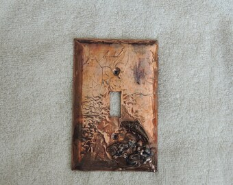 Copper covered light switch plate with fish