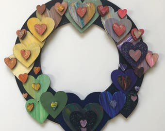 Wooden hand painted muted rainbow heart wreath. Free UK delivery.