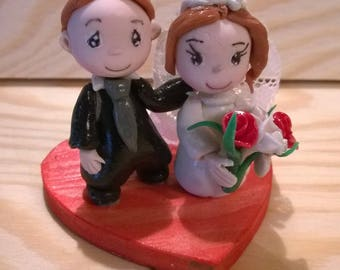 Figurine of marriage: Cake topper character married on heart of cold porcelain.