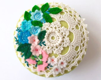 felt pincushion with a vintage style cotton doily, lots of felt flowers and leaves and hand embroidery