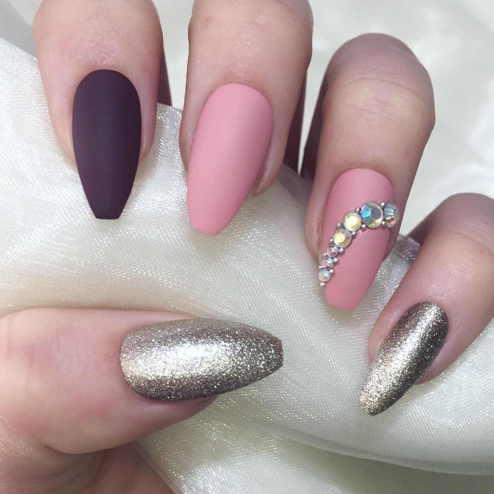 Matte dusty pink champagne and burgundy long coffin nails.
