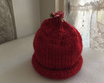 Beautiful hand knit red hat with red and white bow on top for 0-6 month old infants.