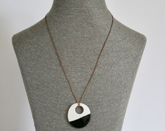 Monochrome porcelain dipped pebble pendant in black and white on leather cord