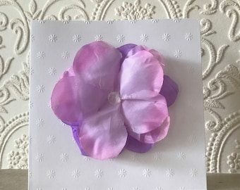Purple and pink fabric flower with gem on embossed card, blank greetings card