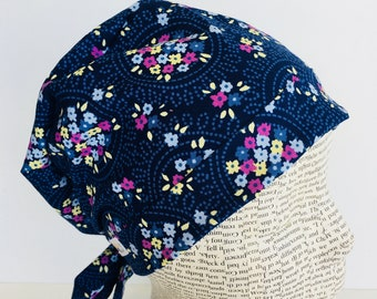 Tie Back Scrub Cap scrub hat featuring a dark blue material with flowers in pink blue and yellow