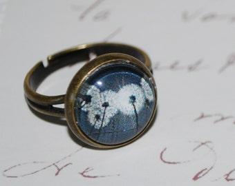 Ring adjustable white dandelions on black background