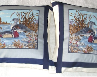 Pair of cushions, Wood Ducks standing on the edge of a lake.