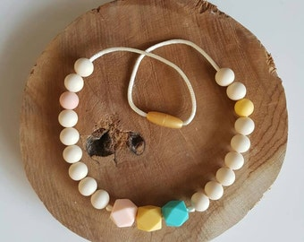 Teething necklace for children of silicone beads. Stress release. Chew need. Safety closure. Chewelry. Teething necklace.