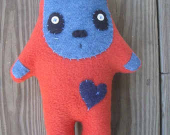 Orange Stretch Monster plushie with little blue heart