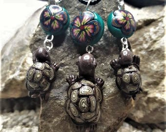 Turtle ornament hanging from a polymer clay bead.