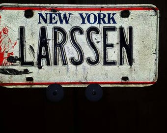 Vintage New York State Vanity License Plate. Blue Letters, White Background, Red Statue of Liberty. Nicely used Condition. Plate ID LARSSEN
