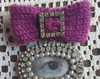 Lover's Eye brooch. Diamante with purple knitted bow