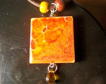 A resin wood pendant necklace, beads glass and waxed cotton cord.