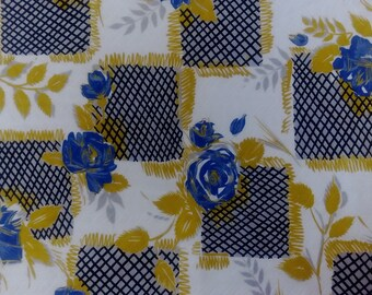 Vintage cotton 1950s quilting or dressmaking fabric, blue roses with mustard leaves on cream background.