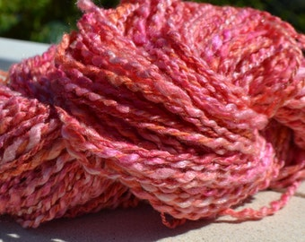 Skein of yarn spun hand shades of pink and orange salmon