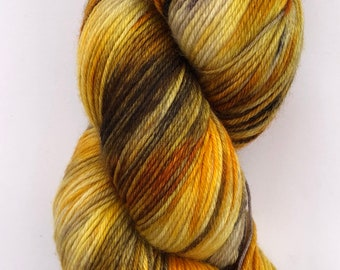 A beautiful, soft hand dyed yarn in shades of golden yellow, orange and brown on a merino, nylon base.