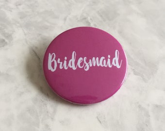 Bridesmaid button badges in pink with white script writing