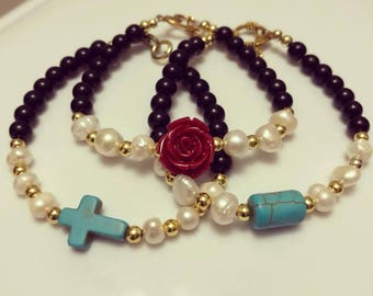 Beaded bracelet with with pearls and red flower.