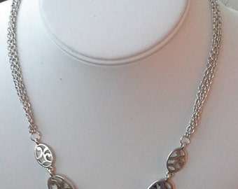 Vintage silver tone necklace with 5 oval ornate links of different sizes.