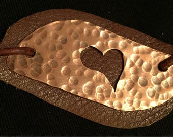 Hand cut and hammered asymmetrical copper necklace with heart cutout oxidation and leather patch