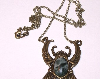 bronze scarab pendant with green and white stone