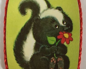 Skunk holding flower magnet, vintage made in 1980's,