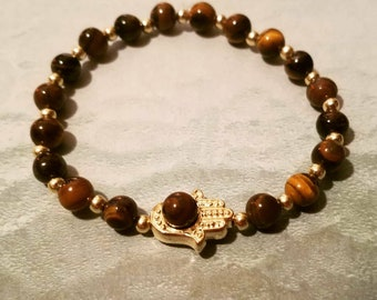 "6mm Tiger eye beads with a gold plated Hamsa Hand. Model's wrist is 6.5""."