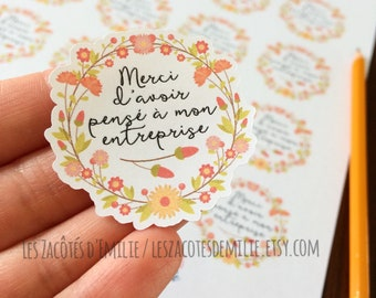 """Sticker """"Merci d'acheter local"""" with a wreath of flowers, on white paper"""