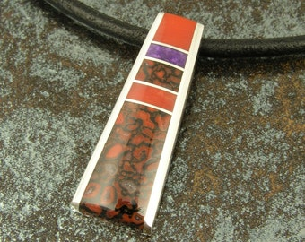 Sterling silver pendant inlaid with coral, sugilite and red dinosaur bone by Mark Hileman.