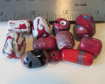 An assortment of predominately red fused  glass lampwork beads