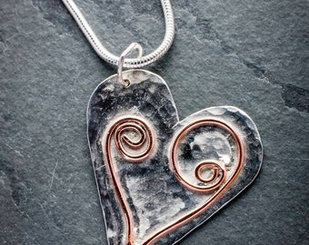 Sterling silver heart shaped pendant with copper wire detail.