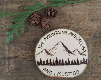The mountains are calling and I must go. Wood burned mountain scene magnet with John Muir quote.