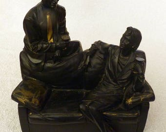 An Art Deco Sculpture of a Period Dressed Man and Woman Sitting On A Sofa