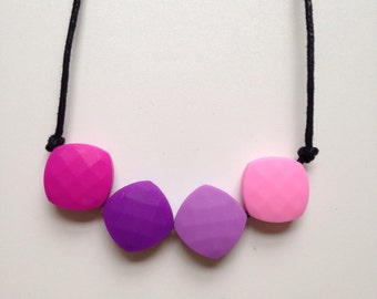 Teething necklace in fuchsia, purple, lilac, pink; made from BPA free chewable silicone quadrate beads by Little Gnashers