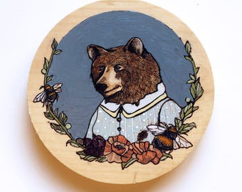 Small round painting of a bear in a dress
